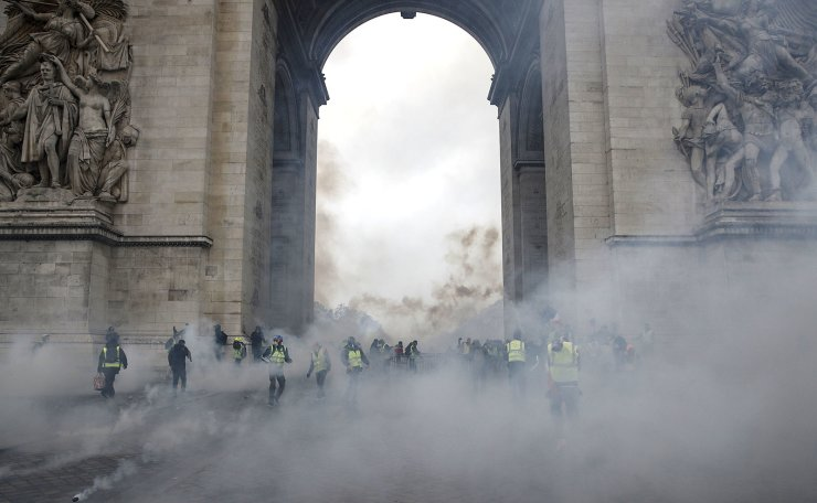 Protesters wearing yellow vests (gilets jaunes) clash with riot police in a cloud of teargas under the Arc de Triomphe during a demonstration over high fuel prices on the Champs Elysee in Paris, France, 01 December 2018. EPA