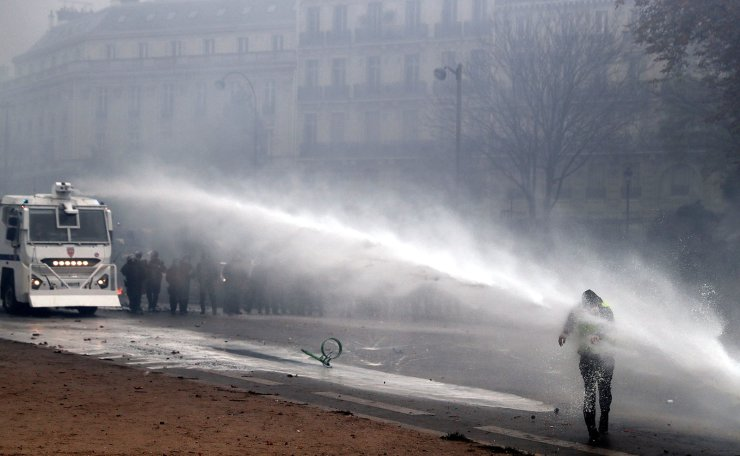 Riot police use a water canon on a protester during clashes near the Arc de Triomphe as part of a demonstration over high fuel prices on the Champs Elysee in Paris, France, 01 December 2018. EPA