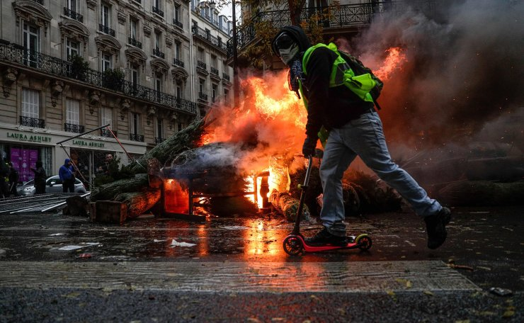 A demonstrator rides past a fire during a protest of Yellow vests (Gilets jaunes) against rising oil prices and living costs, on December 1, 2018 in Paris. AFP