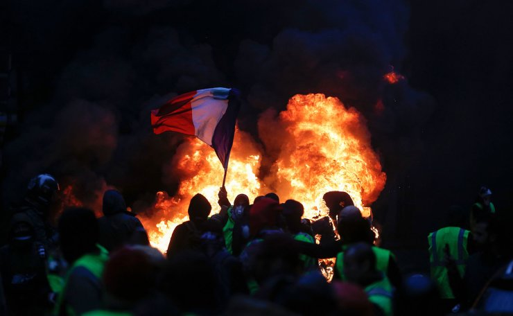 A French flag floats as fire is burning during a protest of Yellow vests (Gilets jaunes) against rising oil prices and living costs, on December 1, 2018 in Paris. AFP