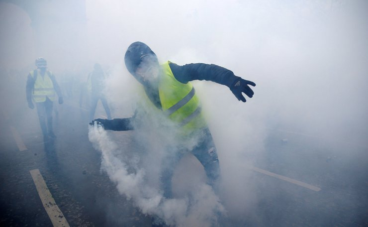 Tear gas fills the air as a protester wearing a yellow vest, a symbol of a French drivers' protest against higher diesel taxes, demonstrates near the Place de l'Etoile in Paris, France, December 1, 2018. Reuters