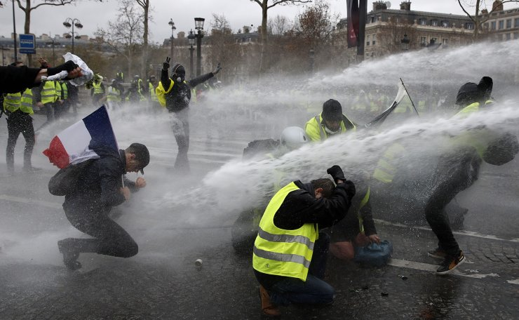 Protesters wearing yellow vests (gilets jaunes) are sprayed with water cannons as they clash with riot police near the Arc de Triomphe during a demonstration over high fuel prices on the Champs Elysee in Paris, France, 01 December 2018. EPA