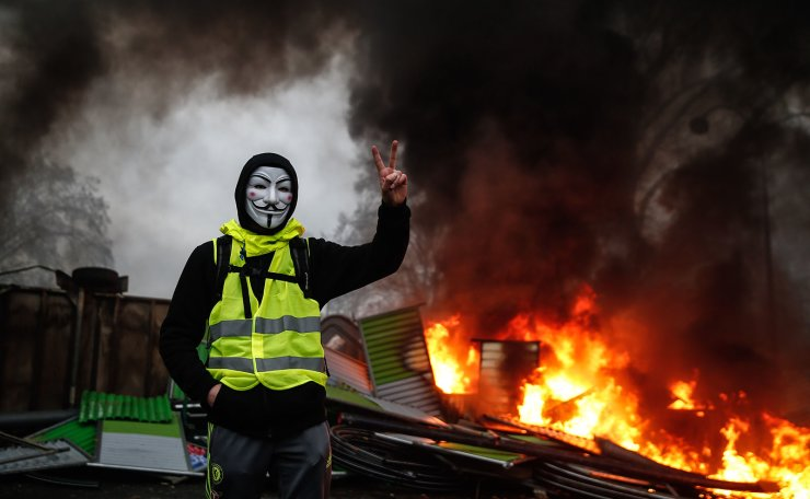 A protester wearing a Guy Fawkes mask makes the victory sign near a burning barricade during a protest of Yellow vests (Gilets jaunes) against rising oil prices and living costs, on December 1, 2018 in Paris. AFP