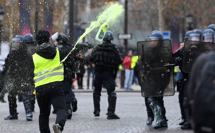 A demonstrator throws a bottle containing yellow painting at riot police officers during a protest of Yellow vests (Gilets jaunes) against rising oil prices and living costs on the Champs Elysees in Paris, on December 1, 2018. AFP