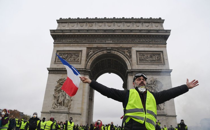 A demonstrator waves a French national flag during a protest of Yellow vests (Gilets jaunes) against rising oil prices and living costs in front of the Arc of Triomphe on the Champs Elysees avenue in Paris, on December 1, 2018. AFP