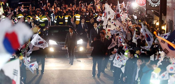 Hundreds of people supporting Park Geun-hye wave the Taegeukgi, the national flag, as the former President's car arrives at her private residence in southern Seoul, Sunday. / Yonhap