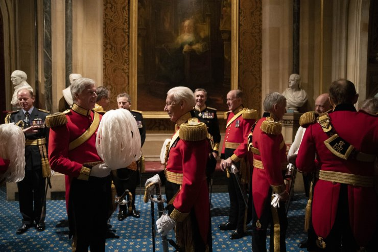 Members of the Honourable Corps of Gentlemen at Arms talk beneath a painting of Britain's Queen Victoria before lining-up in the Norman Porch at the Palace of Westminster and the Houses of Parliament at the State Opening of Parliament ceremony in London, Monday, Oct. 14, 2019. AP