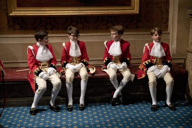 Page boys sit together before lining-up for the arrival of Britain's Queen Elizabeth II in the Norman Porch at the Palace of Westminster and the Houses of Parliament for the State Opening of Parliament ceremony in London, Monday, Oct. 14, 2019. AP