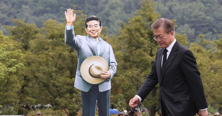 President Moon Jae-in walks by a cardboard cutout of former President Roh Moo-hyun after a speech during a memorial service for the late president at Roh's hometown of Bongha Village, Gimhae, South Gyeongsang Province, Tuesday. Moon was Roh's longtime friend and his chief of staff. / Joint press corps