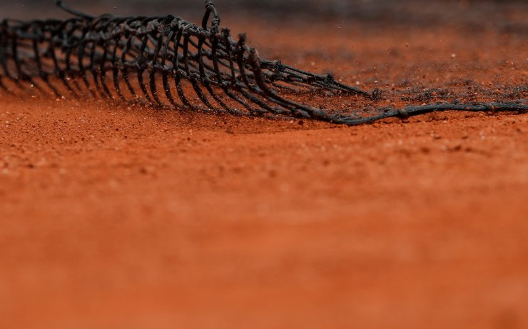 Ground staff wipes the clay court during the break of the men's singles first round match between Rafael Nadal of Spain and Yannick Hanfmann of Germany at French Open tennis tournament 2019 at Roland Garros, in Paris, France on May 27, 2019. Xinhua