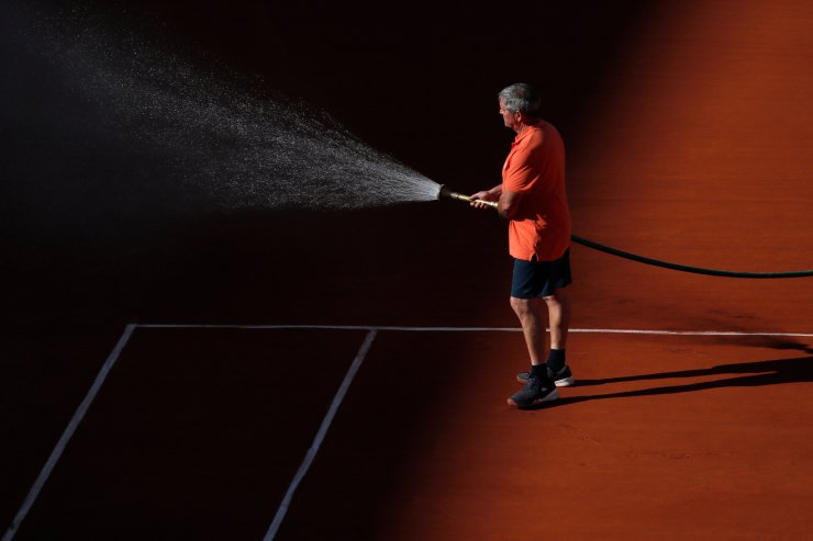 A worker sprays the clay court during third round matches of the French Open tennis tournament at the Roland Garros stadium in Paris, Saturday, June 1, 2019. AP