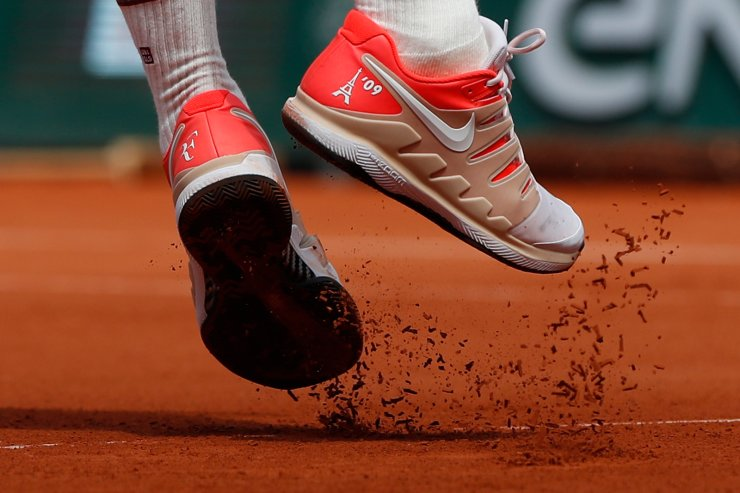 Switzerland's Roger Federer's shoes, one adorned with the Eiffel Tower, kick up clay as he serves in his third round match of the French Open tennis tournament against Norway's Casper Ruud at the Roland Garros stadium in Paris, Friday, May 31, 2019. AP