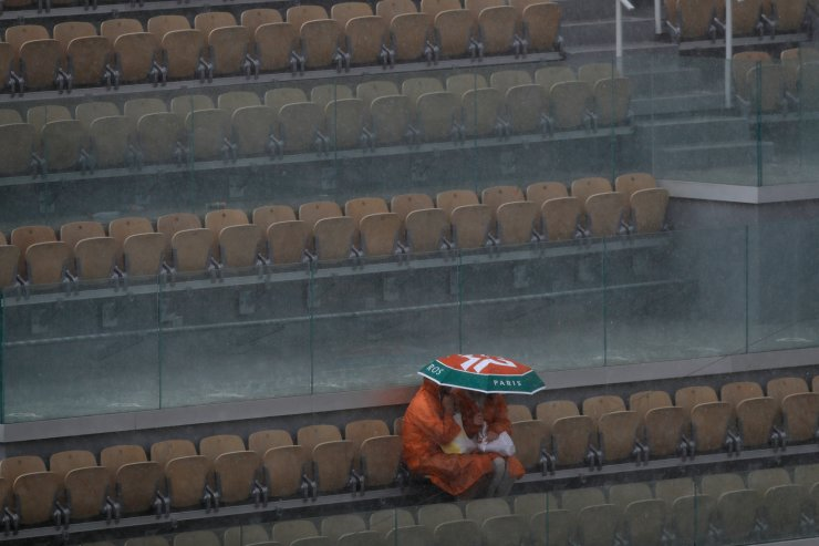 Two spectators take cover during a downpour at center court after the quarterfinal match of the French Open tennis tournament between Japan's Kei Nishikori and Spain's Rafael Nadal was interrupted at the Roland Garros stadium in Paris, Tuesday, June 4, 2019. AP