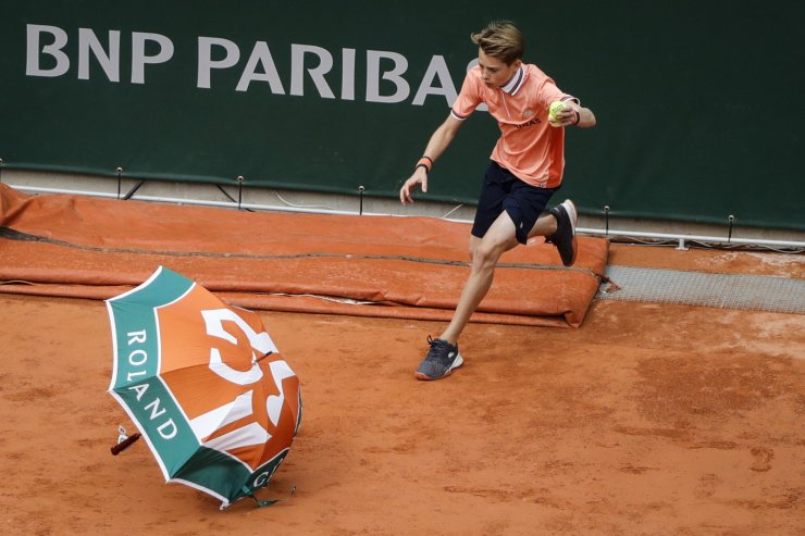 A ball boy collects an umbrella on the court due to heavy wind, during the men's singles semi-final match between Serbia's Novak Djokovic and Austria's Dominic Thiem, on day 13 of The Roland Garros 2019 French Open tennis tournament in Paris on June 7, 2019. AFP