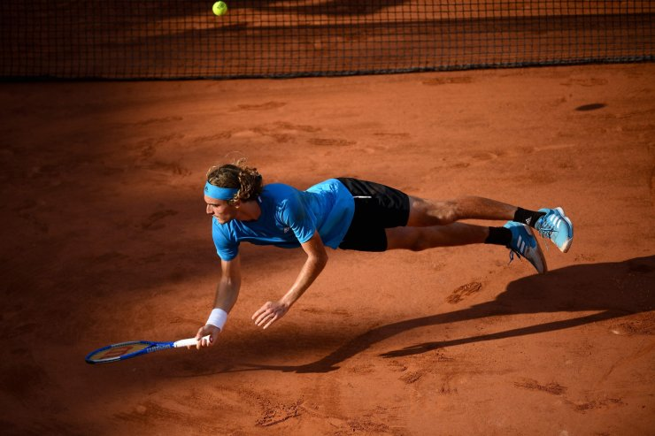 Greece's Stefanos Tsitsipas falls during his men's singles fourth round match against Switzerland's Stanislas Wawrinka on day eight of The Roland Garros 2019 French Open tennis tournament in Paris on June 2, 2019. AFP