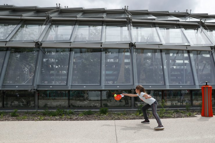 A girl catches a tennis ball with her cap outside the new Simonne Mathieu court at the Jardin des Serres d'Auteuil botanical garden during their first round match of the French Open tennis tournament at the Roland Garros stadium in Paris, Sunday, May 26, 2019. AP