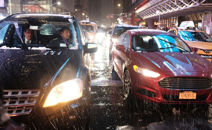 Cars pause at a light as a wintery mix of snow, rain and ice fall during the evening commute in Manhattan on November 15, 2018 in New York City. AFP