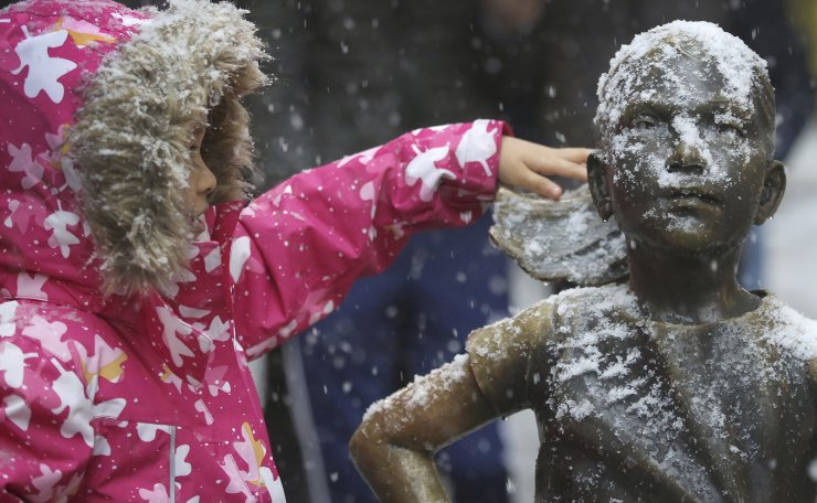 A young girl brushes off snow on the Fearless Girl statue in lower Manhattan on Thursday, Nov. 15, 2018, in New York. AP