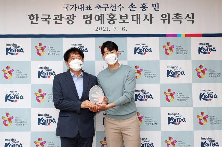 Soccer player Son Heung-min, right, poses with Korea Tourism Organization CEO Ahn Young-bae in Seoul, Tuesday, during a ceremony to appoint him as an honorary ambassador to promote Korean tourism. Courtesy of Korea Tourism Organization