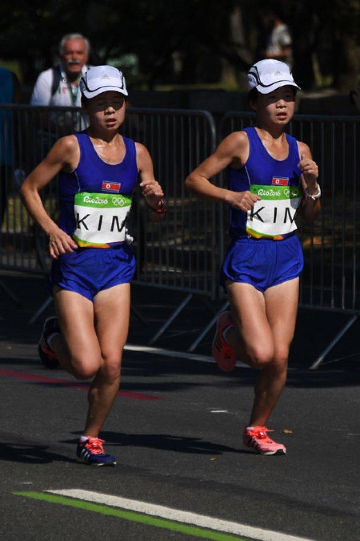 North Korean twin sisters Kim Hye-song and Kim Hye-gyong run together in the women's marathon at Sambodromo in Rio de Janeiro, Monday. / AFP-Yonhap