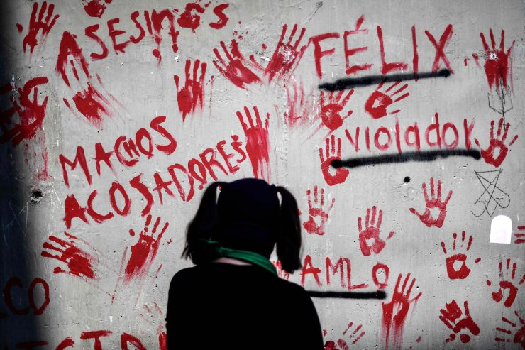 A woman looks at paintings on a wall during a protest for the elimination of violence against women, outside the Investigation Office of Cuauhtemoc Mayor's Office in Mexico City, on March 2, 2021. AFP