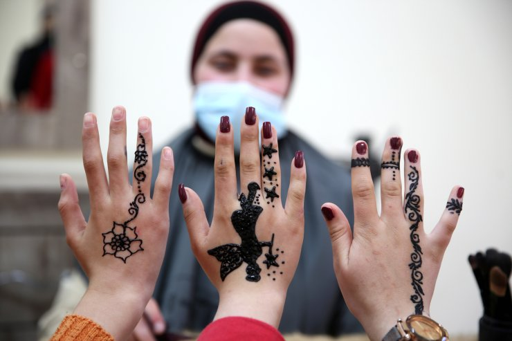 Girls show henna tattoos drawn on their hands by Palestinian henna tattoo artist Samah Sidr at her henna tattoo shop in the West Bank city of Hebron, 07 March 2021, ahead of Women's International day which is celebrated globally on 08 March. EPA