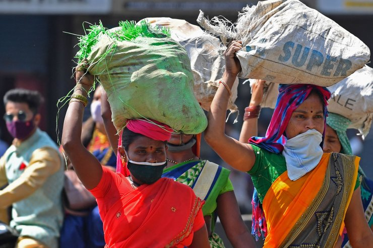 Women carry sacks on their head in Mumbai on March 7, 2021, on the eve of International Women's Day. AFP