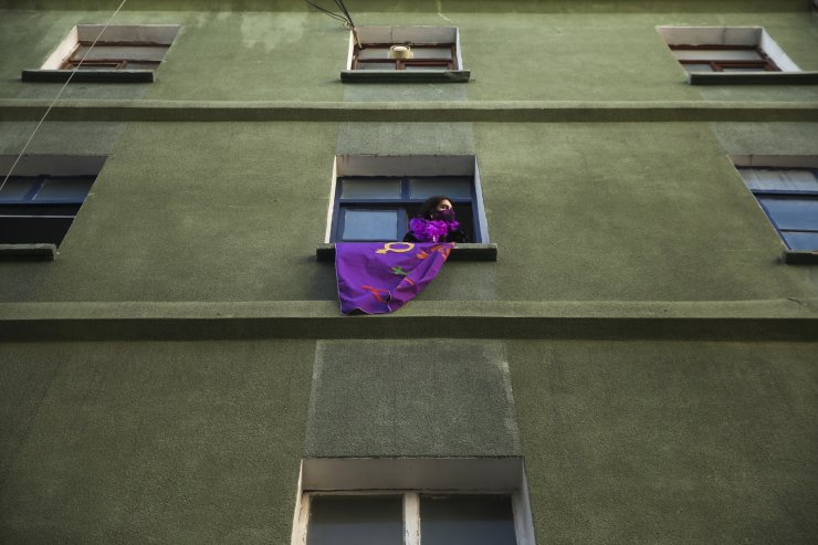 A woman holds a support banner from a window as protesters march to mark International Women's Day in Istanbul, Monday, March 8, 2021.Thousands of people joined the march to denounce violence against women in Turkey, where more than 400 women were killed last year. The demonstrators are demanding strong measures to stop attacks on women by former partners or family members as well as government commitment to a European treaty on combatting violence against women. AP