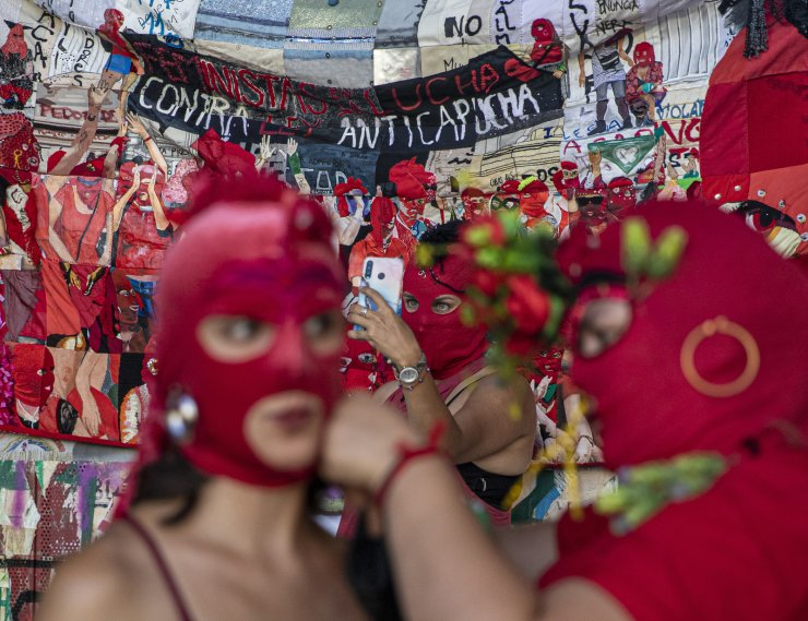 Women put on their masks while another takes a selfie prior to a march for International Women's Day in Santiago, Chile, on Monday, March 8, 2021. AP
