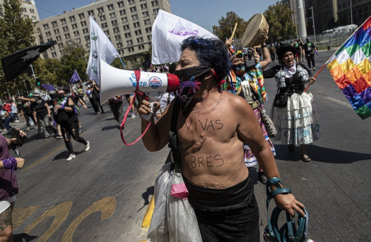 The Spanish message 'Alive and free' covers the torso of a woman shouting slogans against police during a protest marking International Women's Day in Santiago, Chile, Monday, March 8, 2021. AP