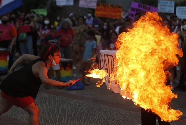 A fire breather burns a poster with the word 'Patriarchy' during a march commemorating Women's International Day in Asuncion, Paraguay, Monday, March 8, 2021. AP