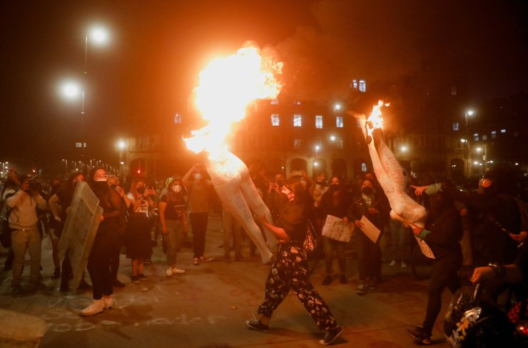 People carry burning mannequins during a protest on International Women's Day, in Mexico City, Mexico, March 8, 2021. REUTERS