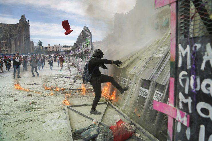 A woman kicks police officers' shields during a protest outside the National Palace to mark International Women's Day in Mexico City, Mexico, March 8, 2021. REUTERS