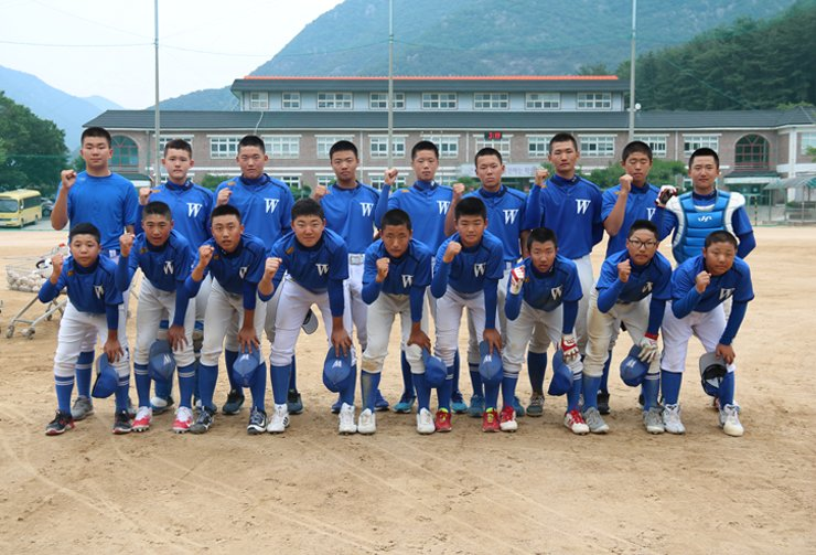 The baseball players of Wondong Middle School in the southeastern city of Yangsan, 310 kilometers southeast of Seoul, pose for a photo with their fists clenched at the school's ballpark on Tuesday. It's the alma mater of Samsung Lions rookie Kim Seong-yoon who drew media frenzy on Sunday for his first home run in the Korea Baseball Organization (KBO) League in a game against the SK Wyverns at the Lions ballpark. Kim is the first Wondong graduate to become a KBO Leaguer. / Korea Times