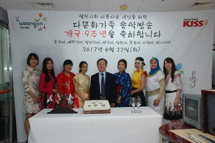 Woongjin Foundation Chairman Shin Hyon-ung, center, poses with radio hosts of a multicultural family music broadcasting station in celebration of its ninth anniversary at its studio in Yeomni-dong, northwestern Seoul, Tuesday. / Courtesy of Woongjin Foundation