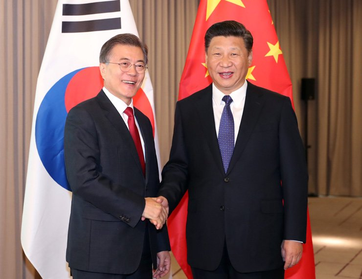 President Moon Jae-in and Chinese President Xi Jinping shake hands ahead of their summit at Intercontinental Hotel in Berlin, Thursday. / Yonhap